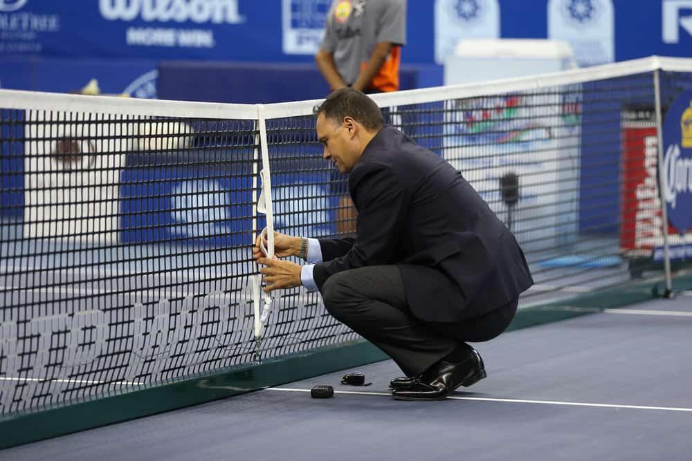 Umpire Mohamed Lahyani of Sweden measures the net height tennis