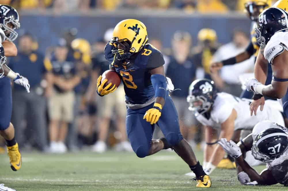 running back Donte Thomas-Williams (8) tries to break free from a tackler football