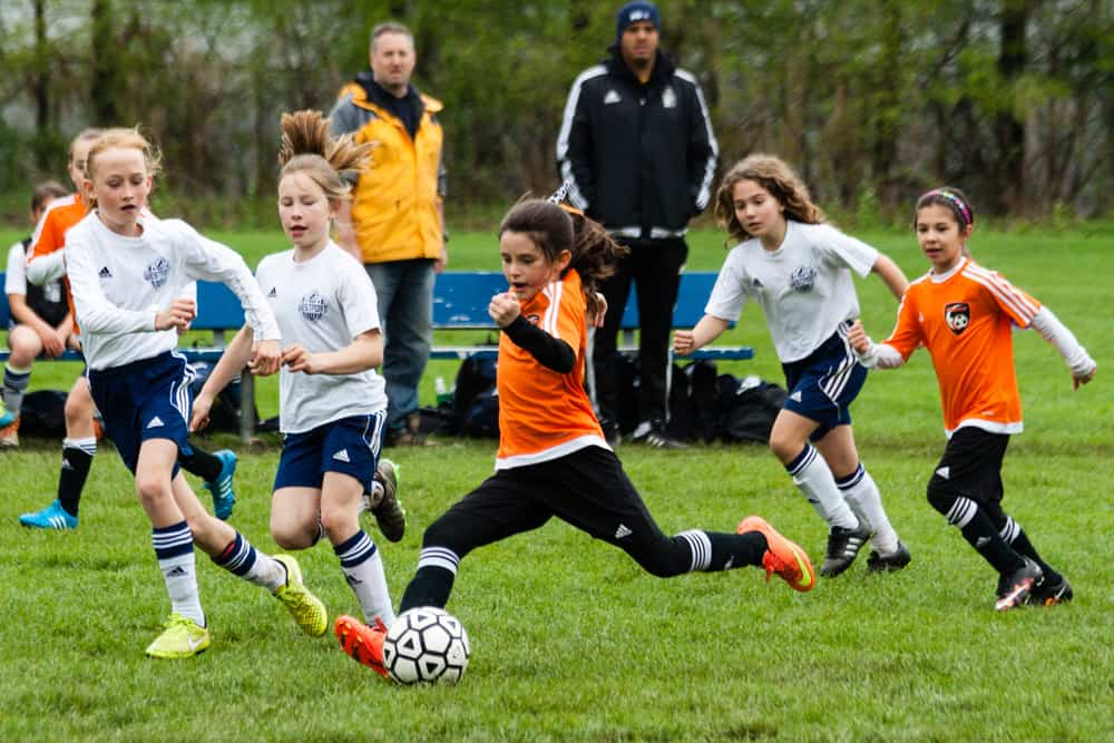 young girls playing an organized youth soccer game