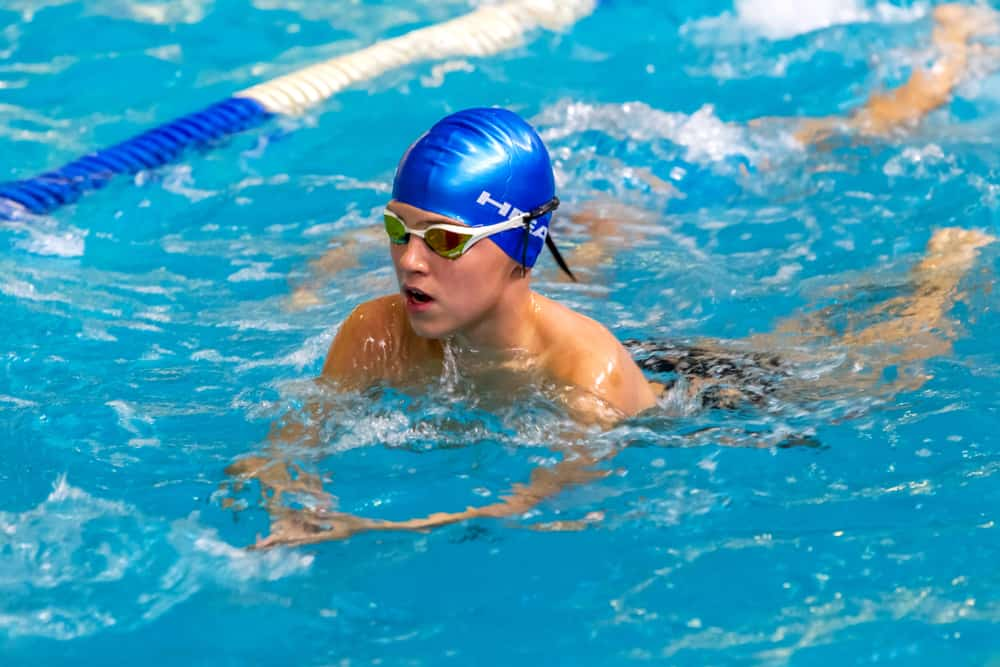 Children, athletes, swimmers swim along tracks in sports pool for swimming