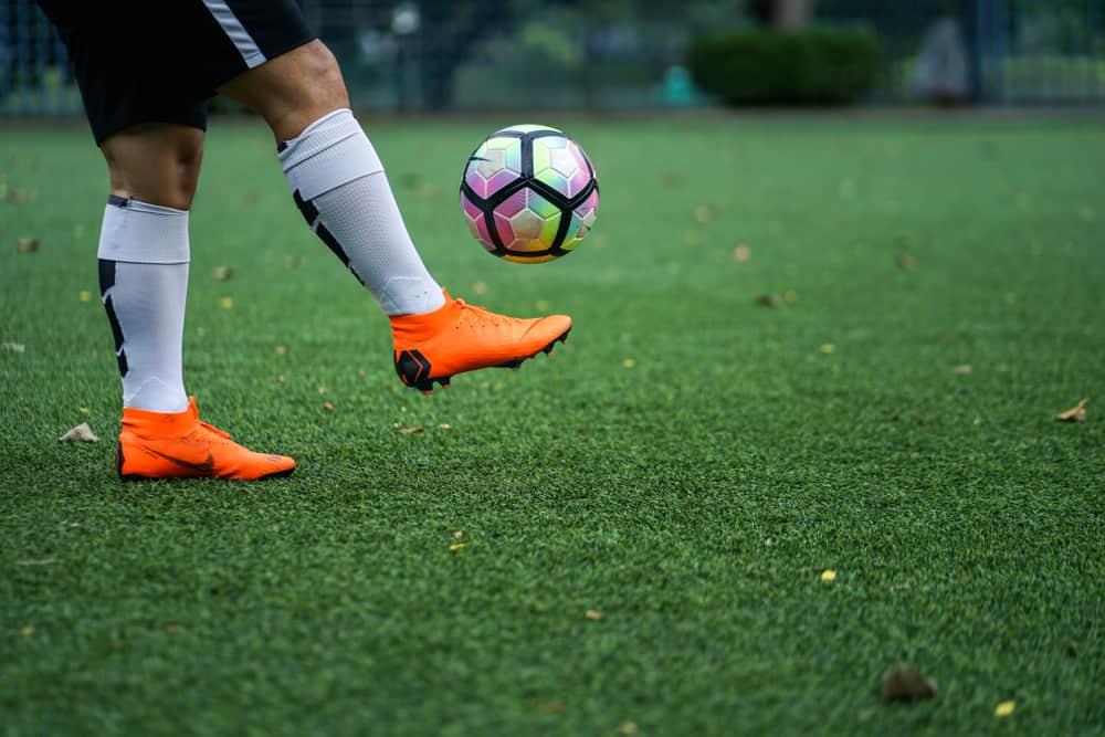 Football player training on artificial grass field