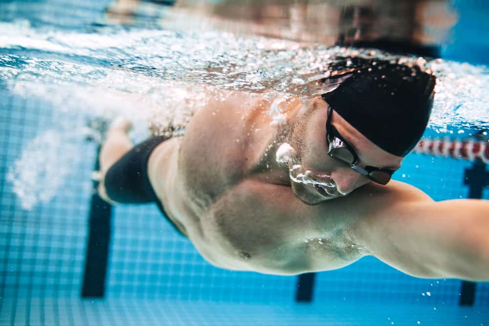 Professional male swimmer practising in swimming pool