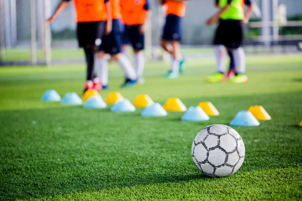 Soccer ball on green artificial turf with blurry of maker cones and players training