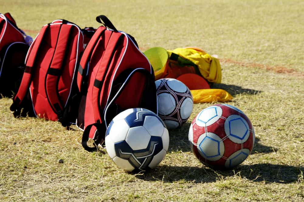 Soccer balls and bags on the sidelines
