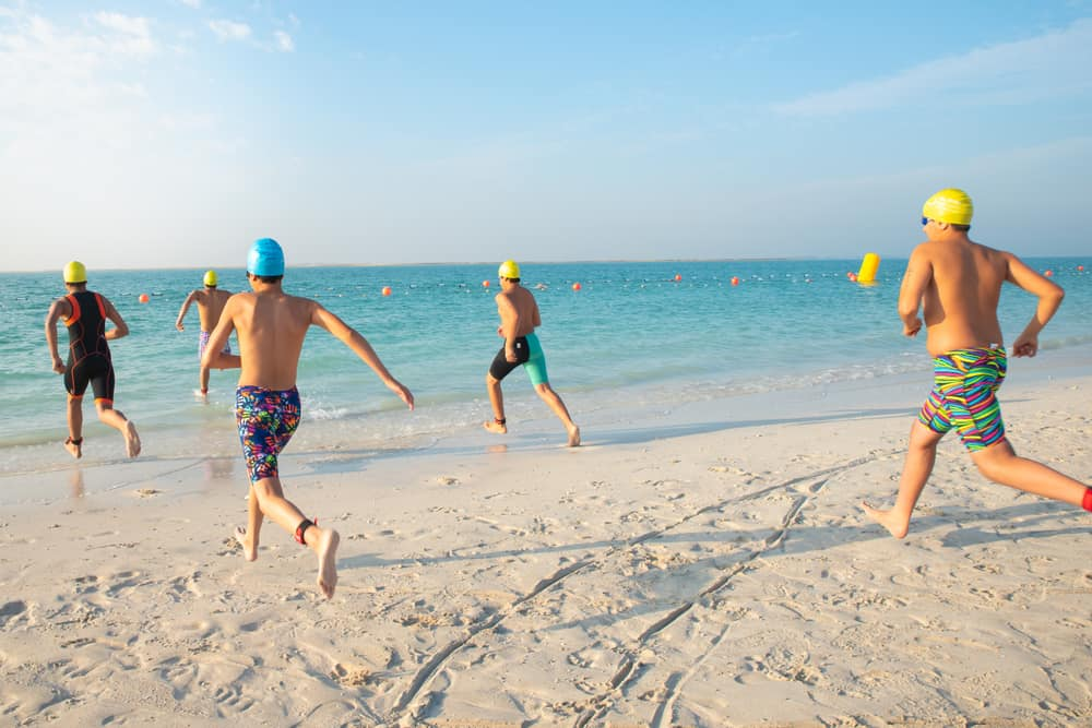 Swimmers running to jump in to the sea for abu dhabi open