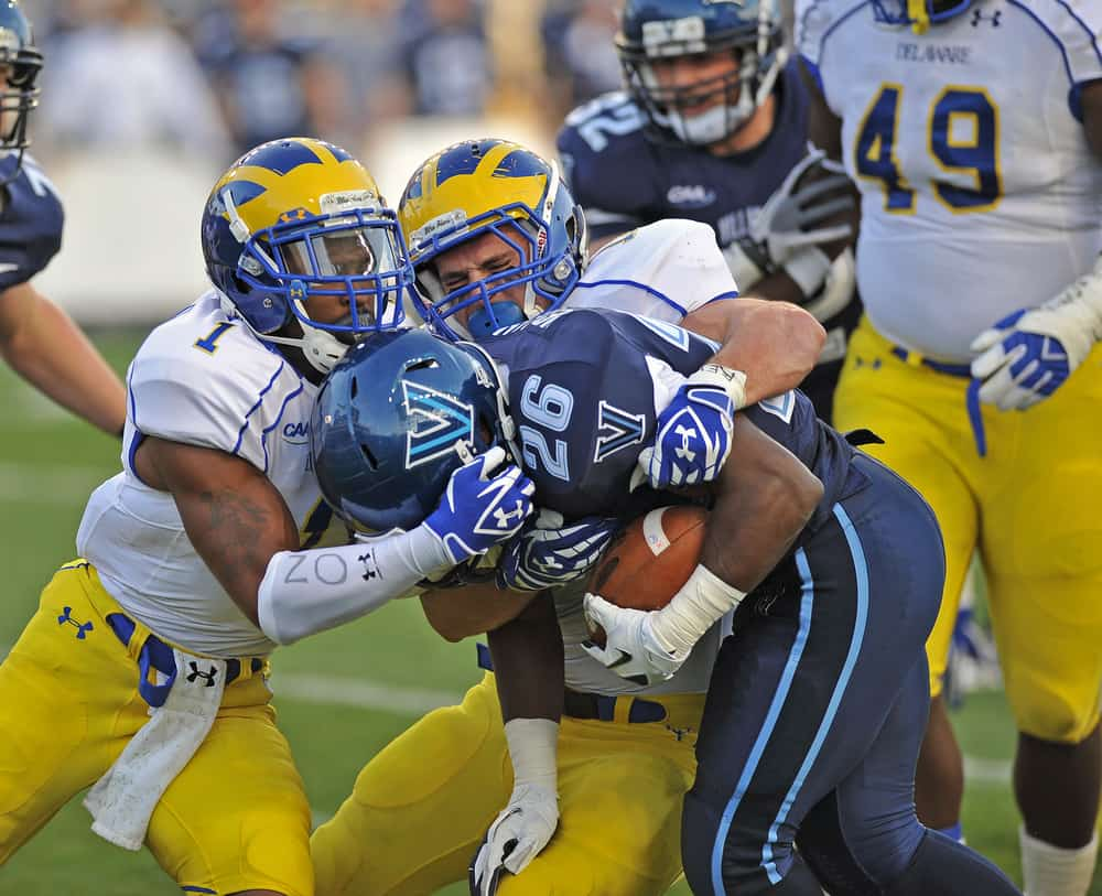 Villanova running back is tackled by two Delaware defenders during NCAA football game