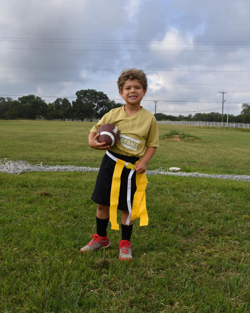 Young boy holding and running with a football during a flag football game