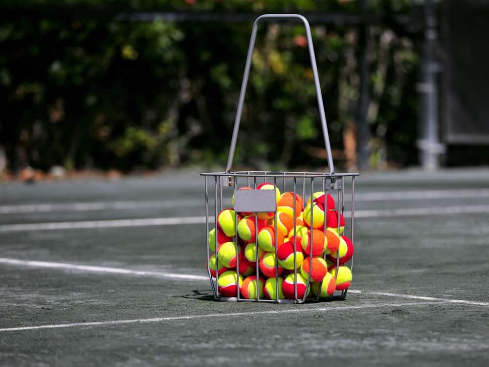 basket of practice tennis balls on tennis court