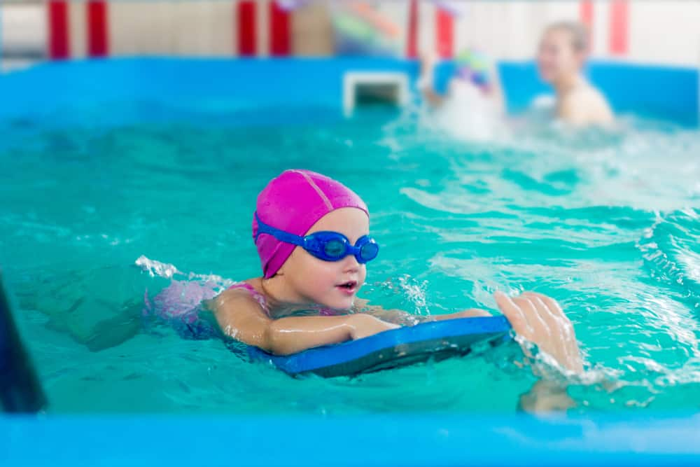 child in a pink rubber hat and blue glasses is swimming in a pool