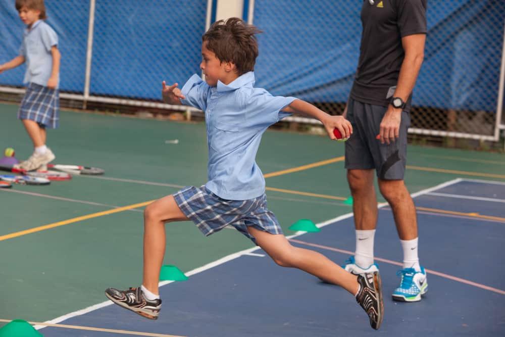 school children take an outdoor tennis lesson