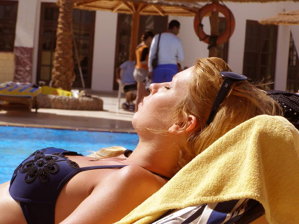 woman lies on a sun lounger with her eyes closed by the pool and tans