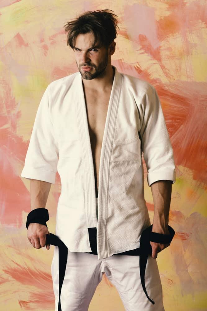 Guy poses in white kimono holding black belt taekwondo