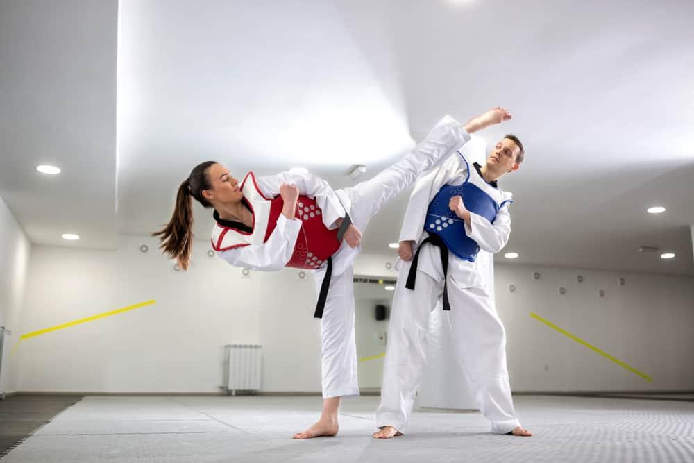 Young woman training martial art of taekwondo with her coach