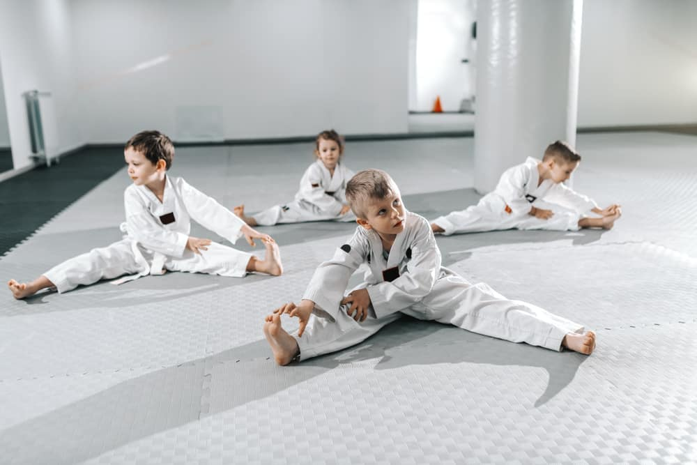 children stretching and warming up before their taekwondo training